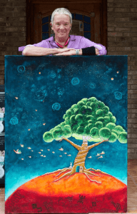 An image of Diane English, the Great Cosmic Happy Ass herself with one of her paintings.