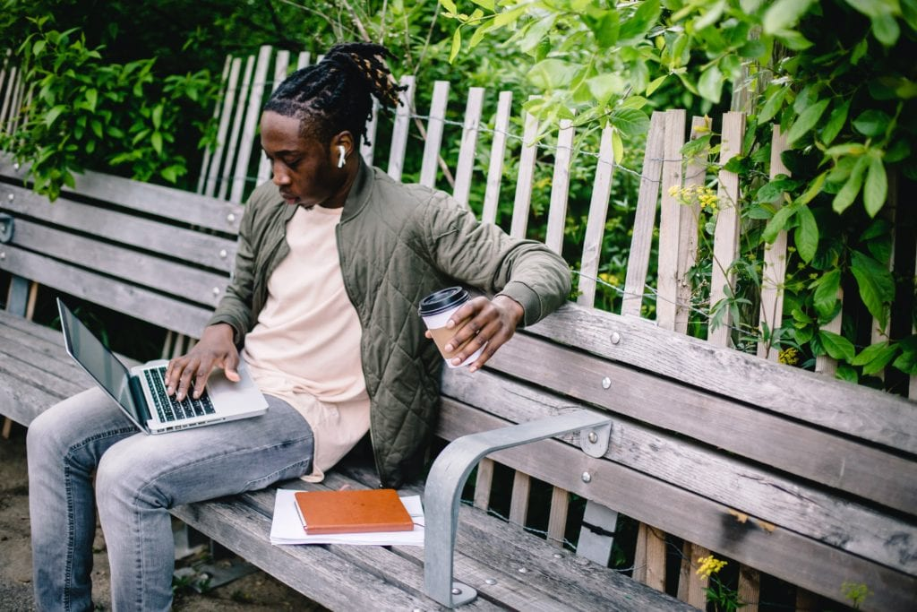 A man consuming content on a park bench in nature