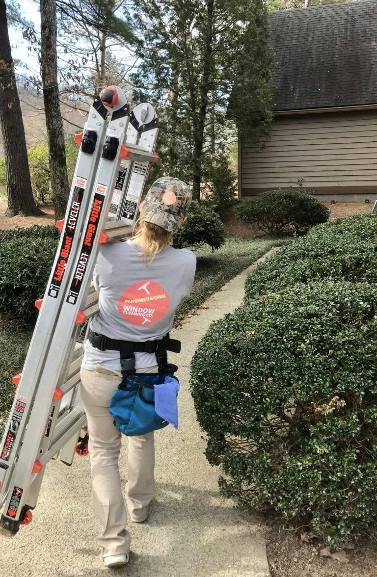picture of a woman carrying ladder: Brevard's Most Trusted + Reliable Window Cleaning Company